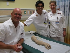 """Students from the Master's Entry Level Professional Nurse (MEPN) program get a helping """"hand"""" with the first-ever clinical skills lab on the CSU Dominguez Hills campus. L-R: Scott Deragisich, Joseph de Veyra, and Poppy Purcell"""