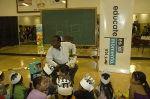 L.A. County Supervisor Mark Ridley-Thomas reads to children at Univision's Feria Es El Momento to teach families about college; photo by Joanie Harmon